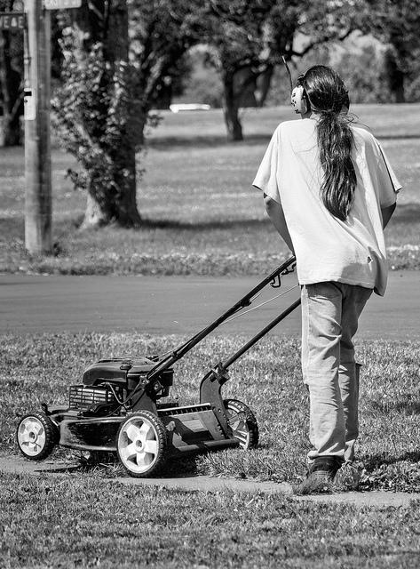 Tyttö ajaa nurmikkoa